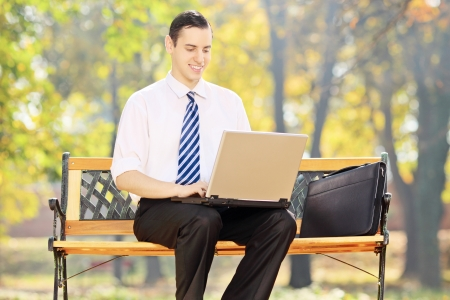 Young businessman sitting on a bench and working on a laptop in a park photo