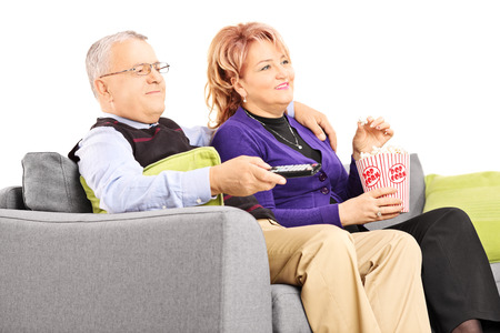 Mature couple watching TV and eating popcorn seated on a sofa, isolated on white  photo