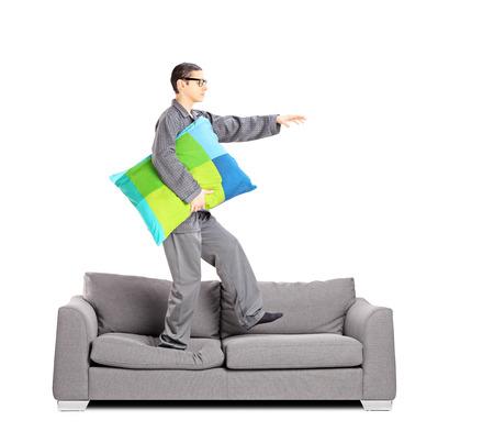 Full length portrait of guy in pajamas sleepwalking on sofa, isolated on white