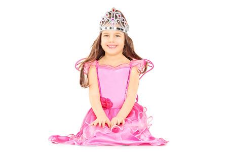 Niña linda vestida como princesa que llevan una tiara aisladas sobre fondo blanco Foto de archivo
