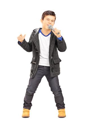 cantando: Retrato de cuerpo entero de un niño cantando en el micrófono aislado en el fondo blanco Foto de archivo