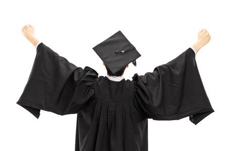 birrete: El estudiante de posgrado en el vestido de la graduación con las manos levantadas aislados en el fondo blanco, vista trasera