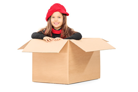 Playful little girl in carton box isolated on white background photo