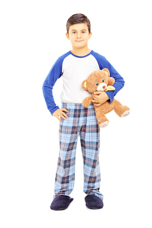 sleepwear: Full length portrait of a boy in pajamas holding teddy bear isolated on white background Stock Photo