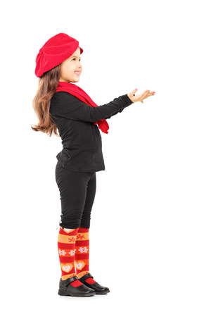 Full length portrait of a cute little girl trying to take something and looking up isolated on white background photo