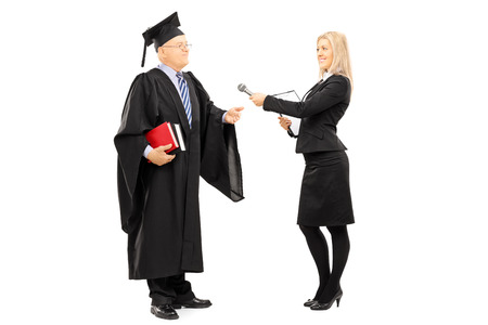 Full length portrait of young female interviewing mature man in graduation gown isolated on white background photo