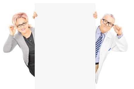 Middle aged woman and male doctor standing behind blank panel isolated on white background photo