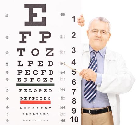 examen de la vista: Hombre que apunta óptica a una prueba de la vista con un palo aislado en el fondo blanco, tiro con inclinación y desplazamiento de la lente Foto de archivo
