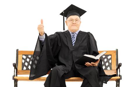 director de escuela: Hombre maduro en traje de graduaci�n sentado en banco de madera que sostiene un libro y que da el pulgar hacia arriba aislados en fondo blanco