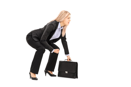 Young businesswoman in sumo wrestling stance holding suitcase isolated on white background
