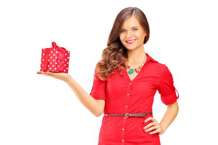 Attractive smiling woman in red dress holding a gift and looking at camera isolated on white background photo