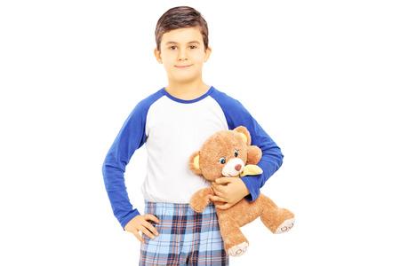 Boy in pajamas holding teddy bear isolated on white background photo