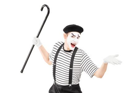 pantomima: Artista Mime que sostiene un bastón y haciendo gestos aislados sobre fondo blanco