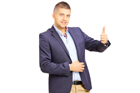 Young man leaning against a wall and giving a thumb up isolated on white background photo
