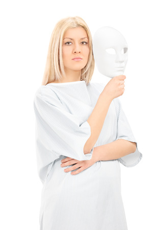 hospital gown: Blond female in hospital gown holding a theater mask and looking at camera isolated on white background