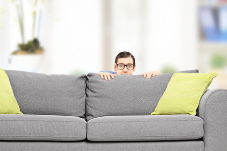 are hidden: Frightened man hiding behind a sofa isolated on white background