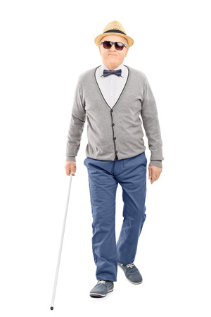 Full length portrait of blind senior gentleman walking with a stick isolated on white background