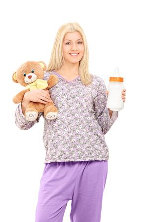 pijama: Mujer joven en pijamas que sostienen el oso de peluche y una botella de bebé aislado en fondo blanco