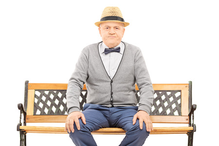 frowned: Senior gentleman with hat seated on bench looking at camera isolated on white background