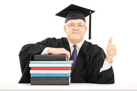 dean: Middle aged college professor seated on table with stack of books and giving thumb up isolated on white background Stock Photo