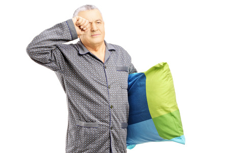 late 50s: Sleepy middle aged man in pajamas holding a pillow isolated on white background