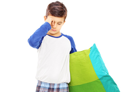 Sleepy kid holding a pillow isolated on white background photo