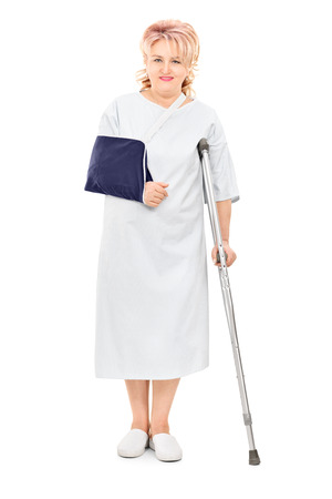 crutch: Full length portrait of female patient with broken arm standing with a crutch isolated on white background