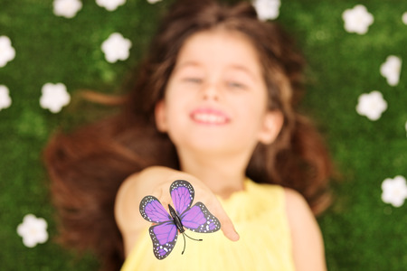 butterfly hand: Blurred photo of little girl laying in meadow with flowers and reaching her hand to touch a purple butterfly Stock Photo