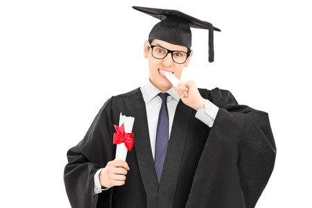 Male college graduate biting his worthless diploma isolated on white background photo