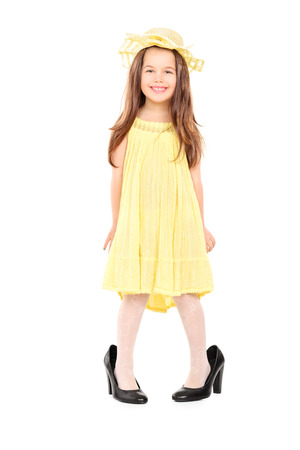 Full length portrait of adorable little girl in fancy yellow dress and hat standing in oversized high heels isolated on white background photo