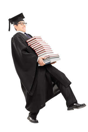 Full length portrait of young man in graduation gown carrying bunch of books isolated on white background photo