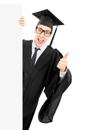 posing  agree: Male college graduate peeking behind blank panel and giving thumb up isolated on white background