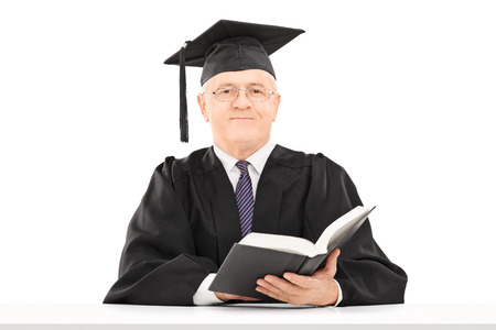 dean: Mature man in graduation gown holding a book and looking at camera isolated on white background