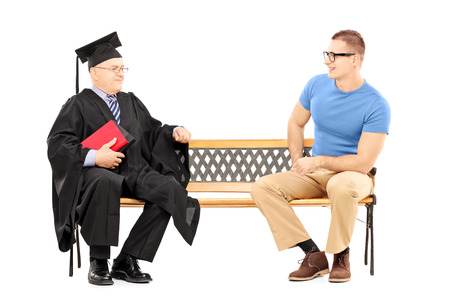 hombre sentado: Hombre joven hablando con un profesor universitario sentado en el banco aislado en blanco