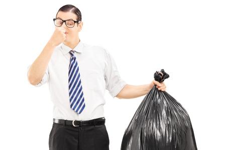 black tie: Mujer cerrando la nariz y la celebraci�n de una bolsa de basura apestosa aisladas sobre fondo blanco