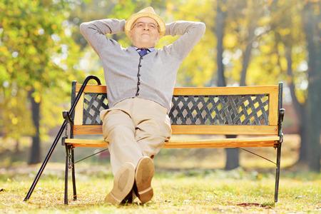 banc de parc: Monsieur aîné Relaxed assis sur un banc dans un parc sur une journée ensoleillée Banque d'images