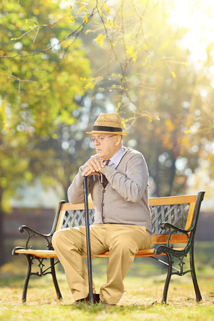 dissappointed: Sad senior man with a cane sitting on bench in a park on a sunny day