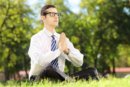 Young businessman doing yoga exercise seated on a grass in a park photo