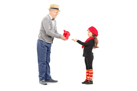 Full length portrait of grandfather giving present to his little niece isolated on white background photo