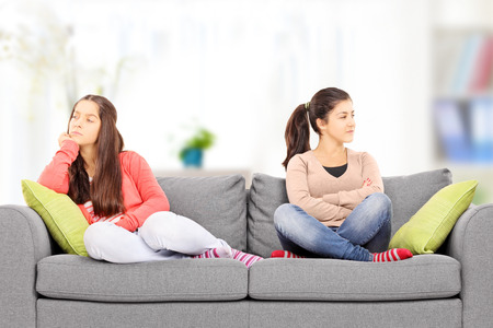 Two teenage girls sitting on sofa, at home, angry with each other