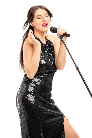 Beautiful woman in black dress singing on microphone isolated on white  photo