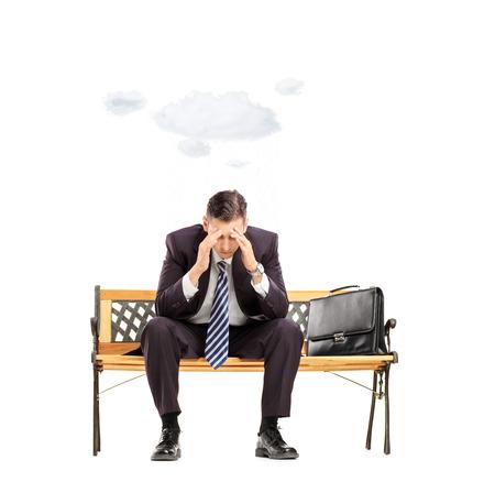 hombre sentado: Hombre de negocios joven preocupante que se sienta en el banquillo con la nube sobre la cabeza aislado en blanco disparó con inclinación y desplazamiento de la lente Foto de archivo
