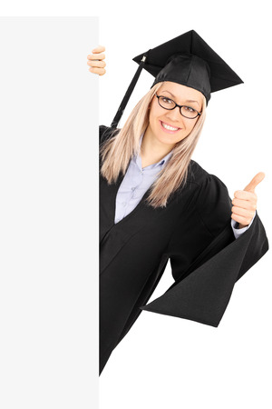 Young woman in graduation gown posing behind blank panel and giving thumb up isolated on white  photo