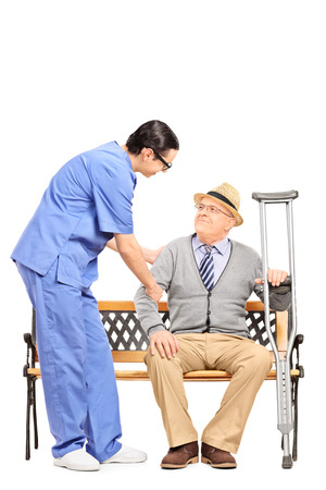 nursing staff: Male healthcare professional assisting a senior gentleman seated on bench isolated on white