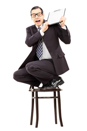 climbed: Scared businessman climbed on chair and swinging with clipboard isolated on white  Stock Photo