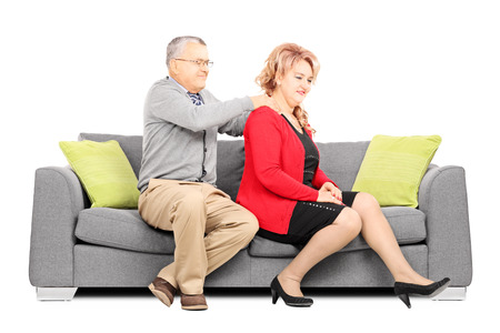 Mature man giving a back rub to his wife seated on couch isolated on white  photo
