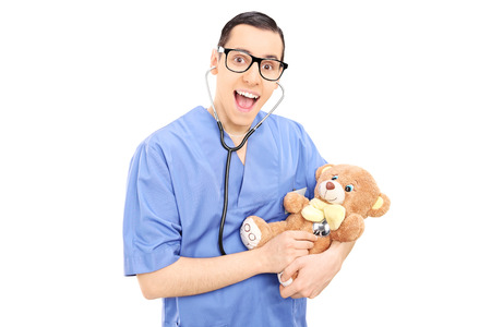 Young male doctor doing medical check on a teddy bear isolated on white  photo