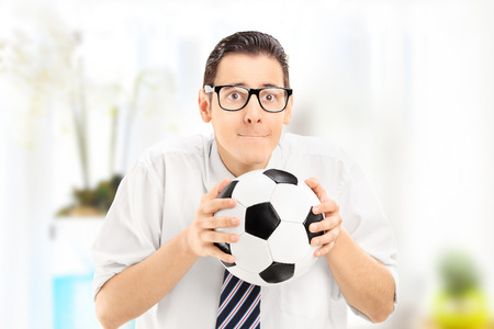 expectations: Anxious young sports fan watching football match and holding a ball, at home