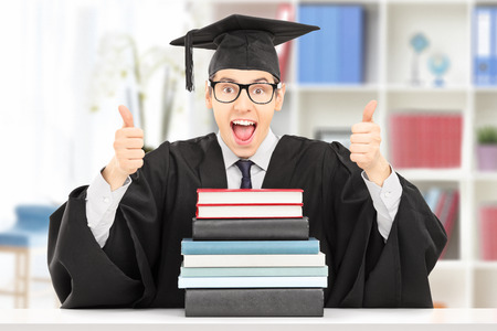 Excited college graduate giving thumbs up seated at table behind a stack of books, indoors photo