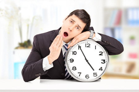 Sleepy young businessman leaning his head on a big wall clock, indoors photo